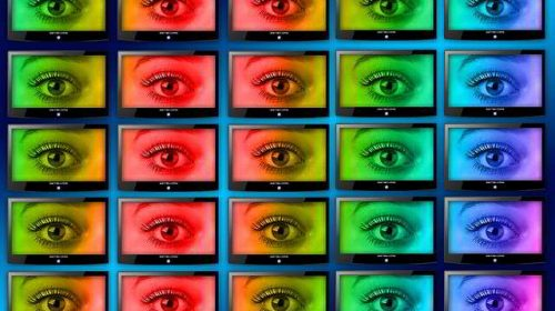 control wall with monitors displaying an eye in different colors