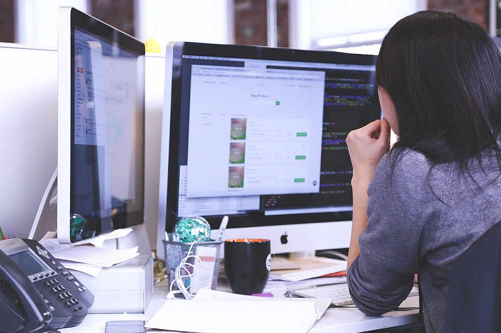 woman on desk watching two monitors with websites